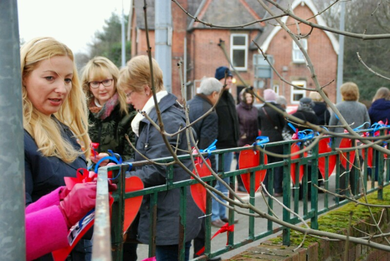 Protesters tie hearts to the school railings